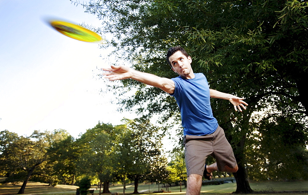 Closeup of a man making a backhanded drive playing disc golf. (Motion Blur)