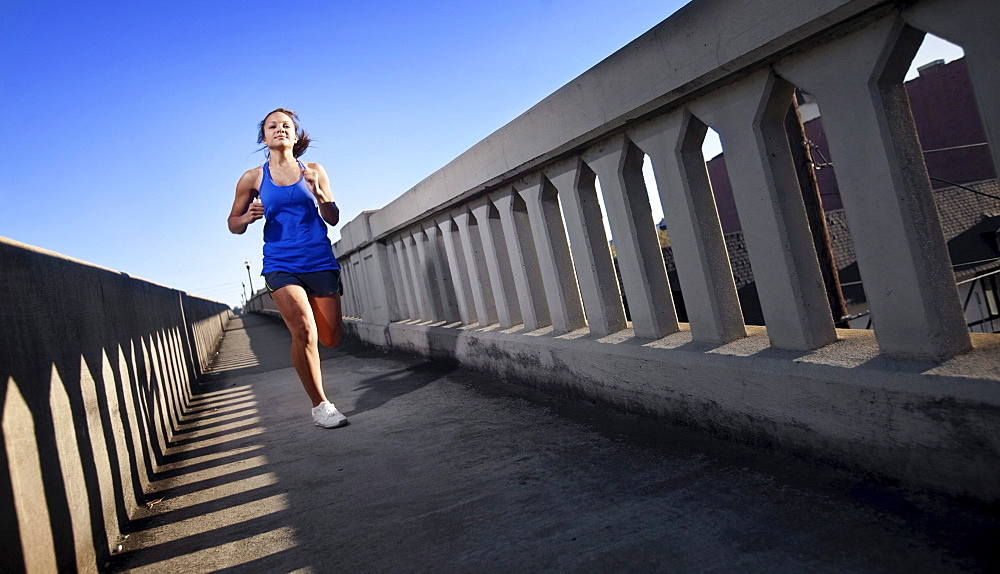 A teenage girl runs on the sidewalk of a bridge in downtown Birmingham, Alabama.