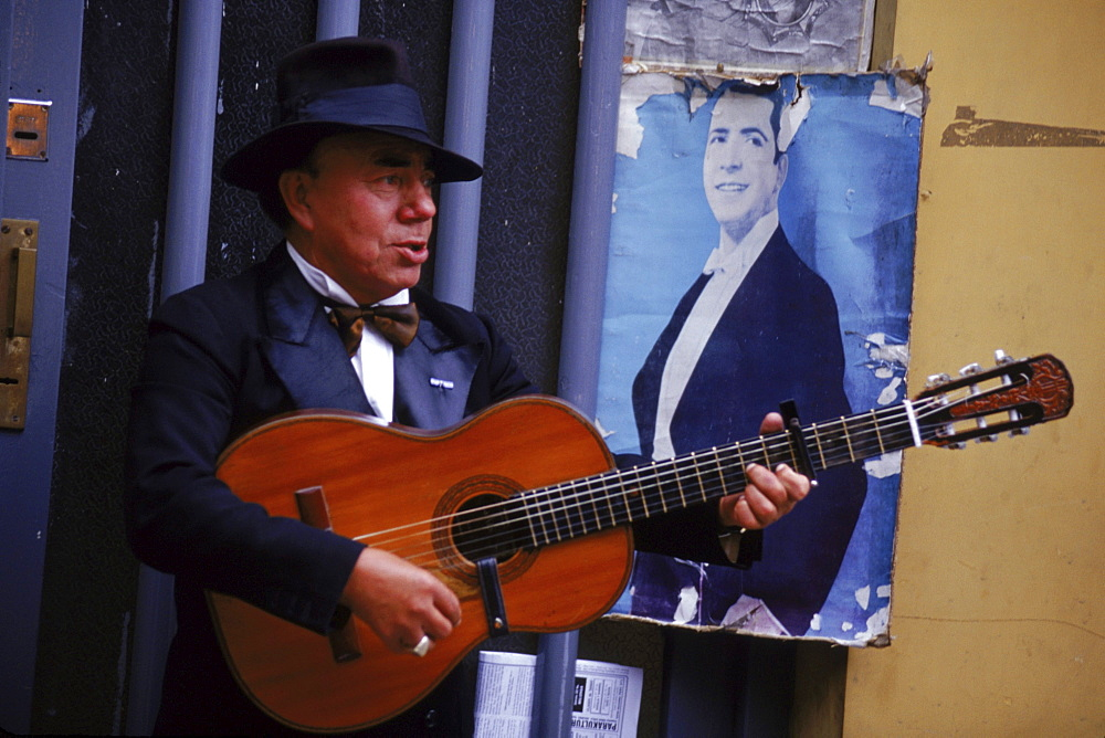 A guitar player strumming for impromptu tango dancers in Buenos Aires' San Telmo Square.