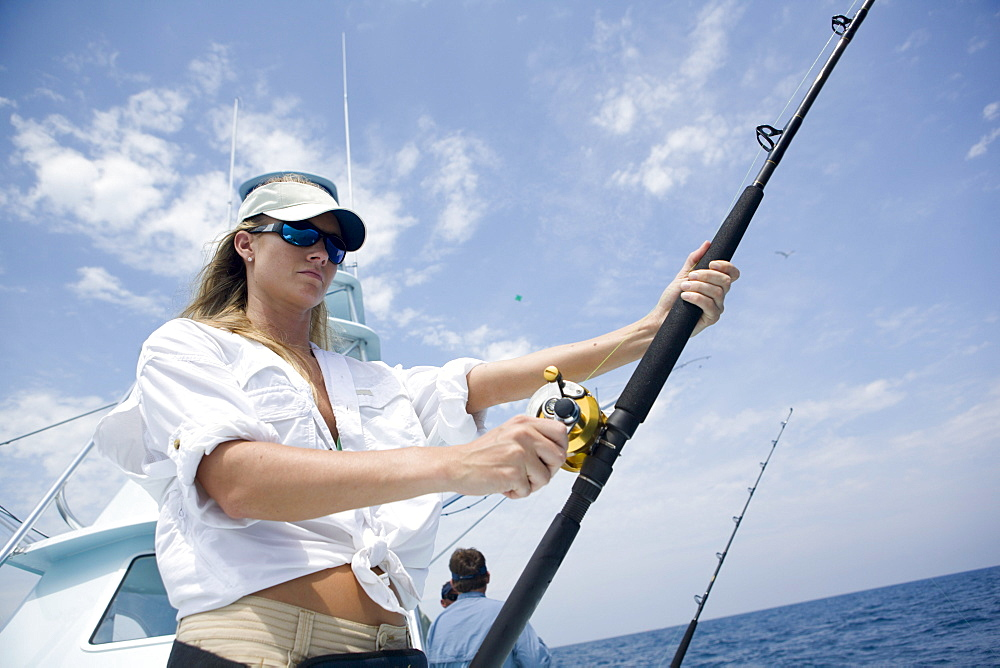 A blonde woman holds a fishing rod while watching for a sailfish to bite.