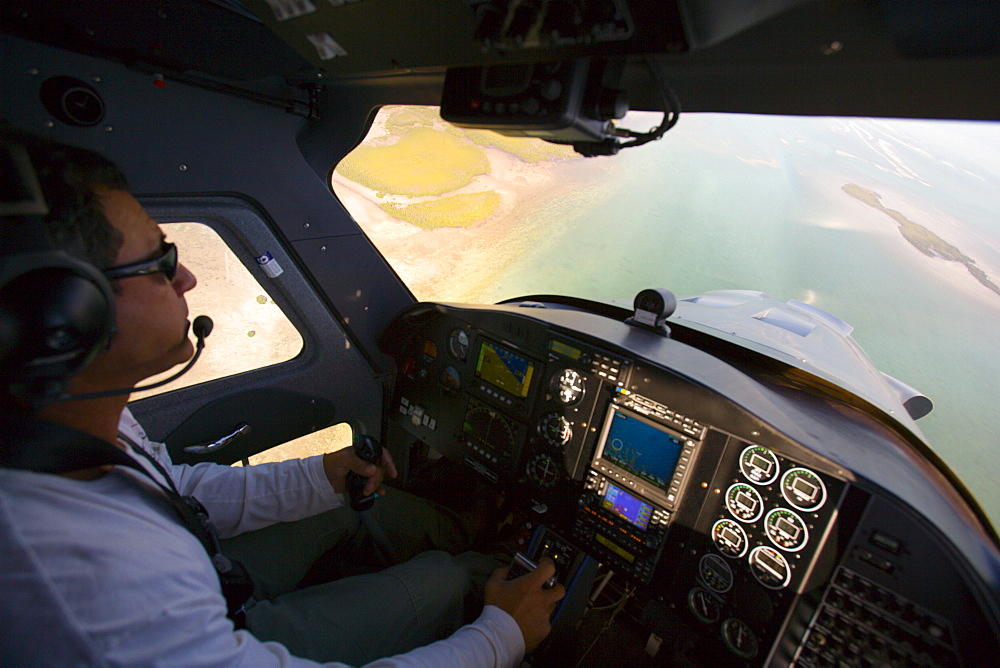 A cockpit view of a pilot looking down at the florida keys.