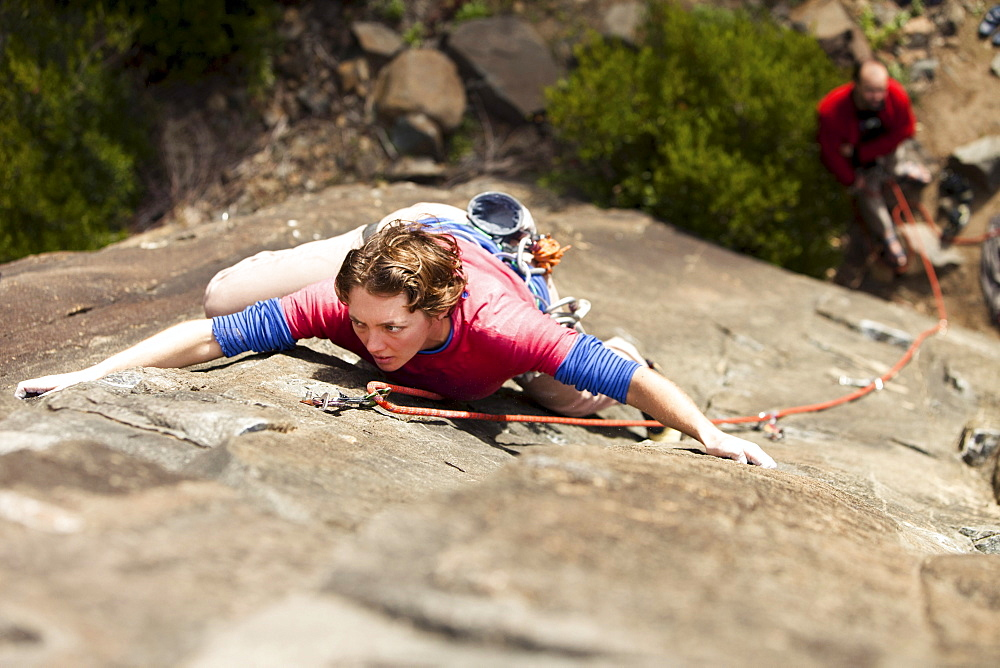 An adult female climber shows her game-face on a route in Australia.
