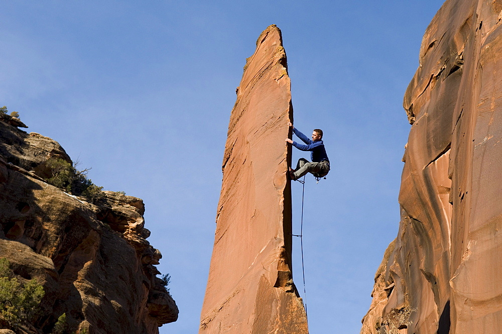 Man rock climbing up slender sandstone spire, Gateway, Colorado.