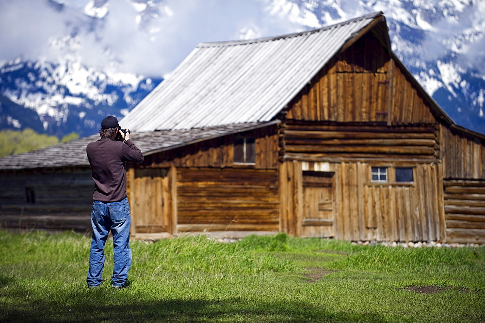 A photographer takes a picture of a historic barn on Mormon Row in Grand Teton National Park, Wyoming.