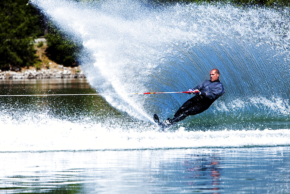 A happy fit man waterskies in a wet suit in Idaho.