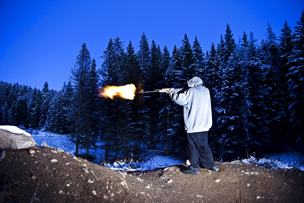 A young man shooting a large gun with a flame coming out of the barrel in Bozeman, Montana.