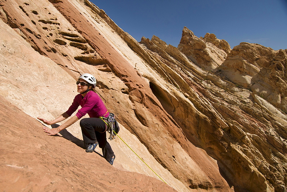 A woman rock climbing up a colorful sandstone slab at the Reef, San Rafael Swell, Green River, Utah.