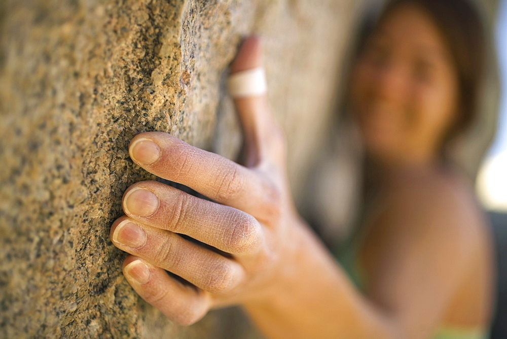 A female climber's hand on rock.