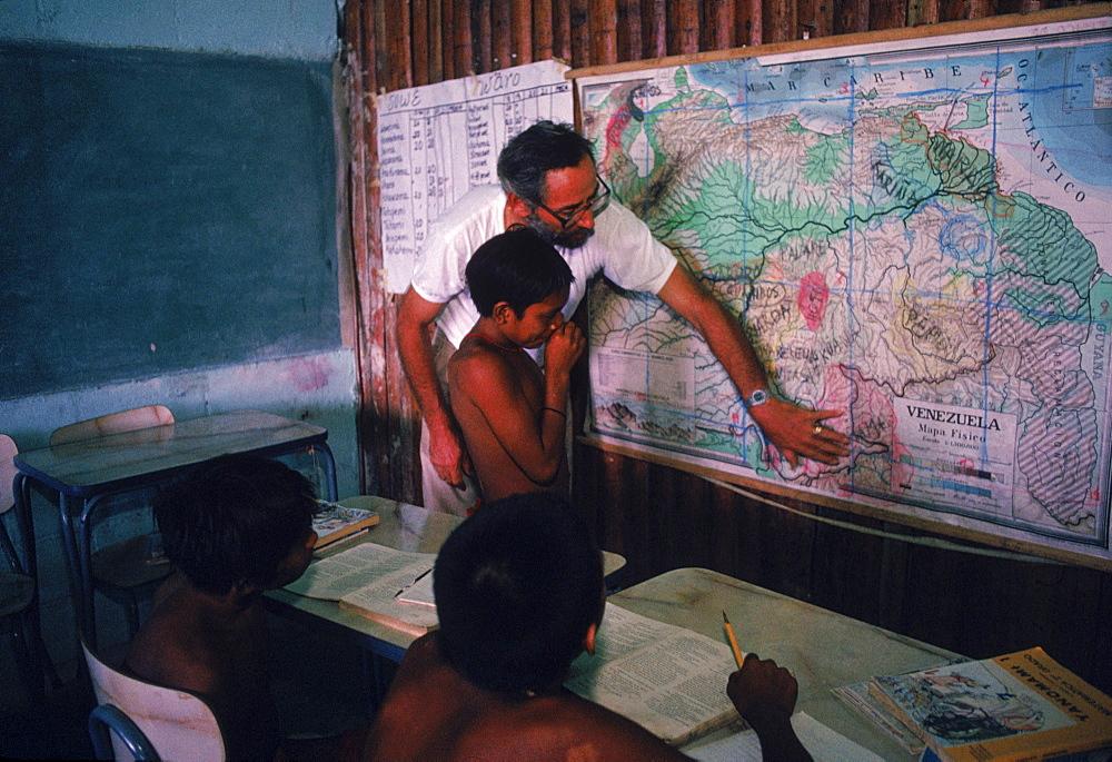 Father Bortoli teaching Yanomami Indian children at the Catholic mission school at Mavaca on the Upper Orinoco River. In the Amazonian Forest in southern Venezuela.