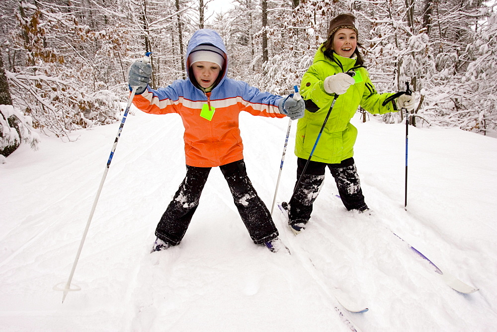 Two young girls Cross Country Skiing in Dayton, Maine.