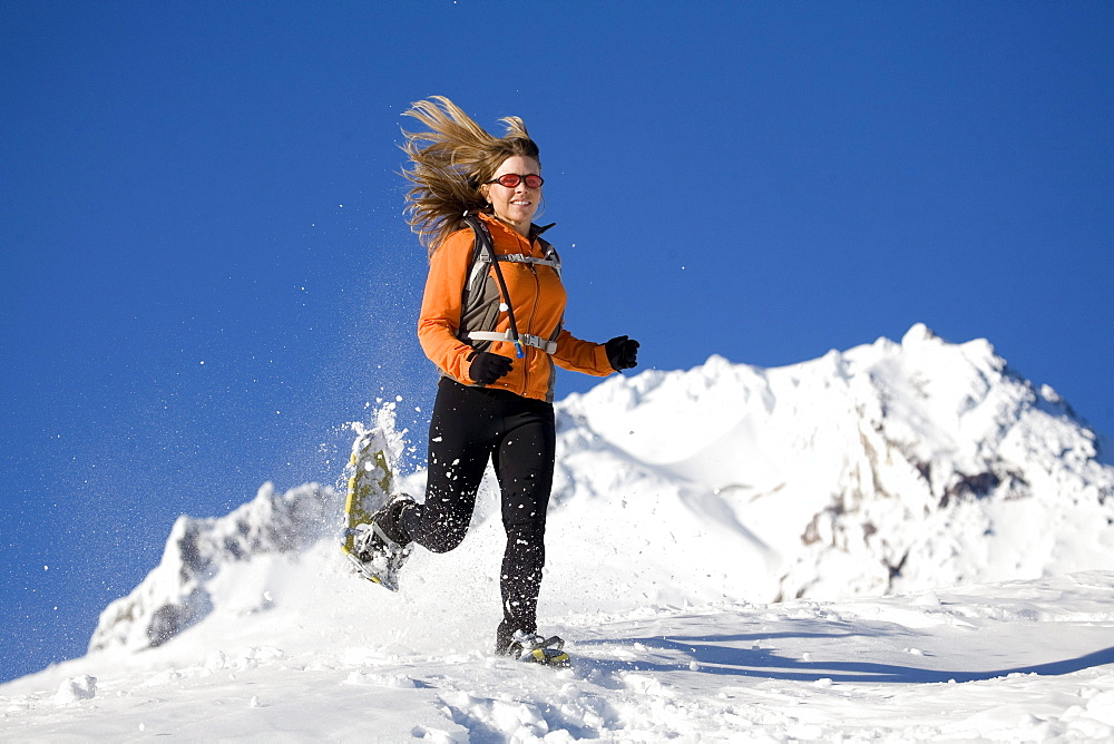 Woman runs with snowshoes in snow.