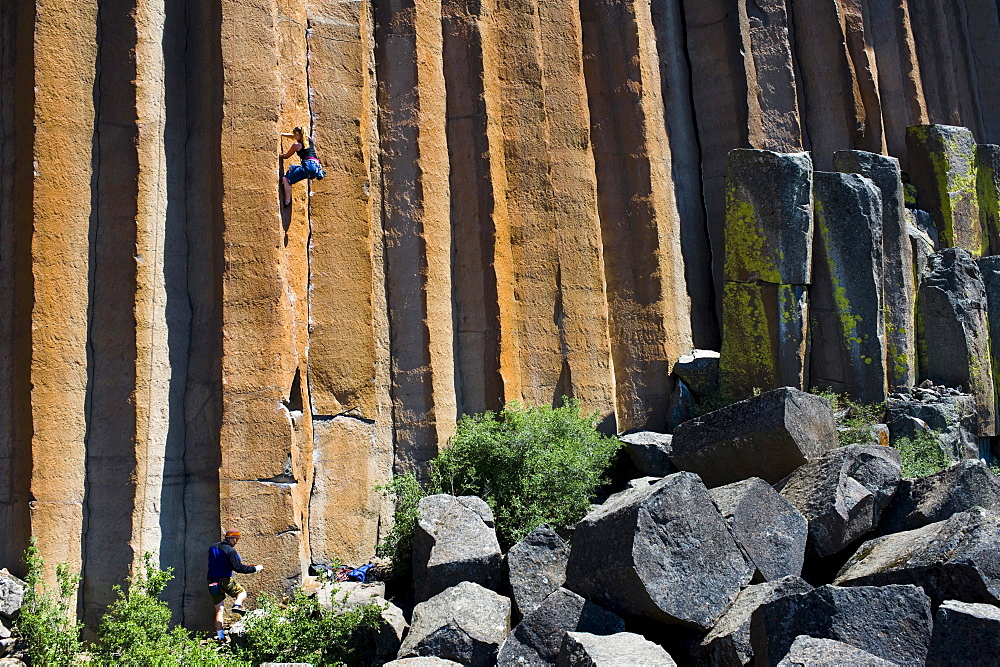 A young woman rock climbing while a mid adult man belays at Trout Creek, Oregon.
