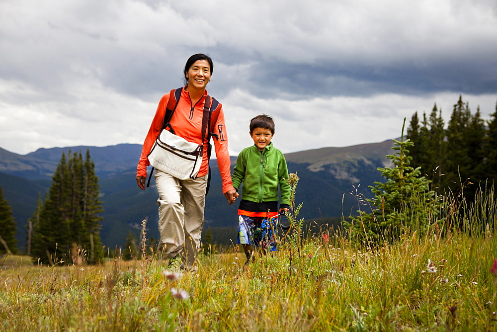 A mid-thirty year old Japanese-American mother walks with her five year old son through a meadow of wild flowers on the way to Lower Crystal Lake, Colorado.