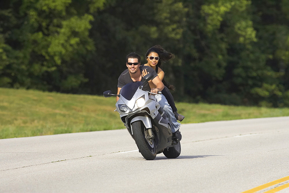 Young couple ridding a sport bike on a country road in Kansas