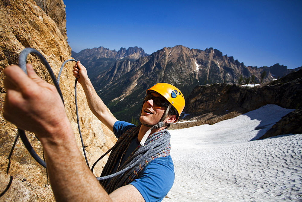 A male climber prepares to lead a pitch on a rocky peak overlooking a snowy valley, Washington, United States of America