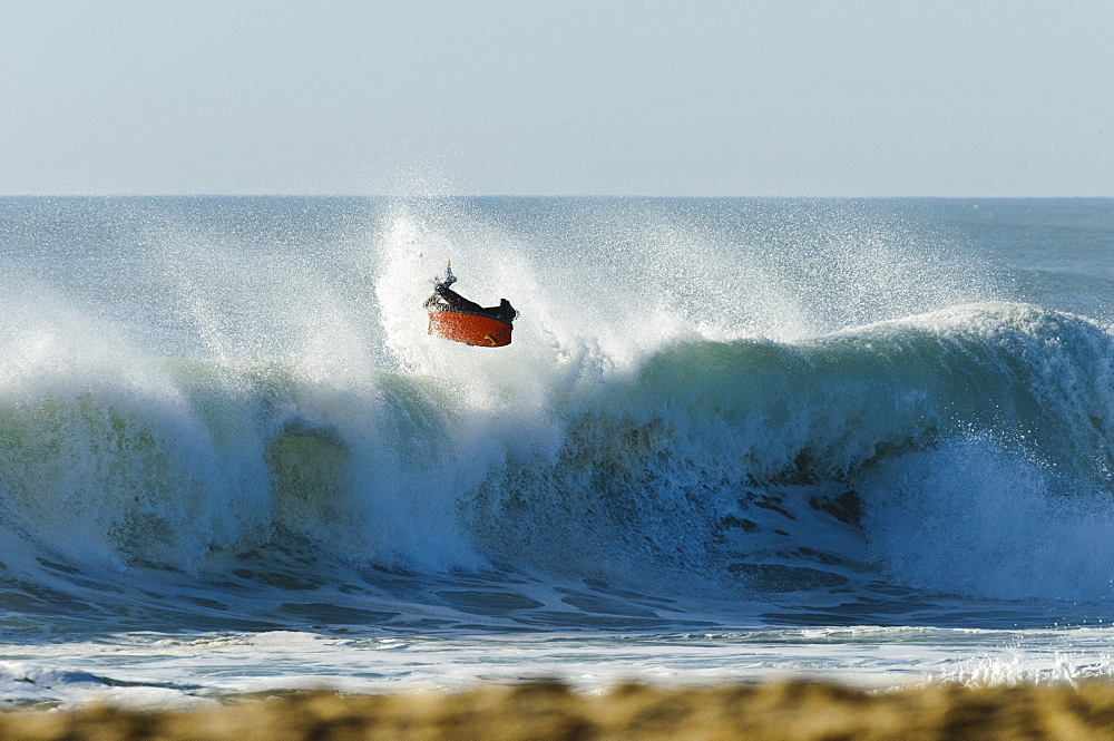 Bodyboarder does a massive air reverse, backlite by the sunset, at Nazare Special Edition, held in Nazare, Portugal.