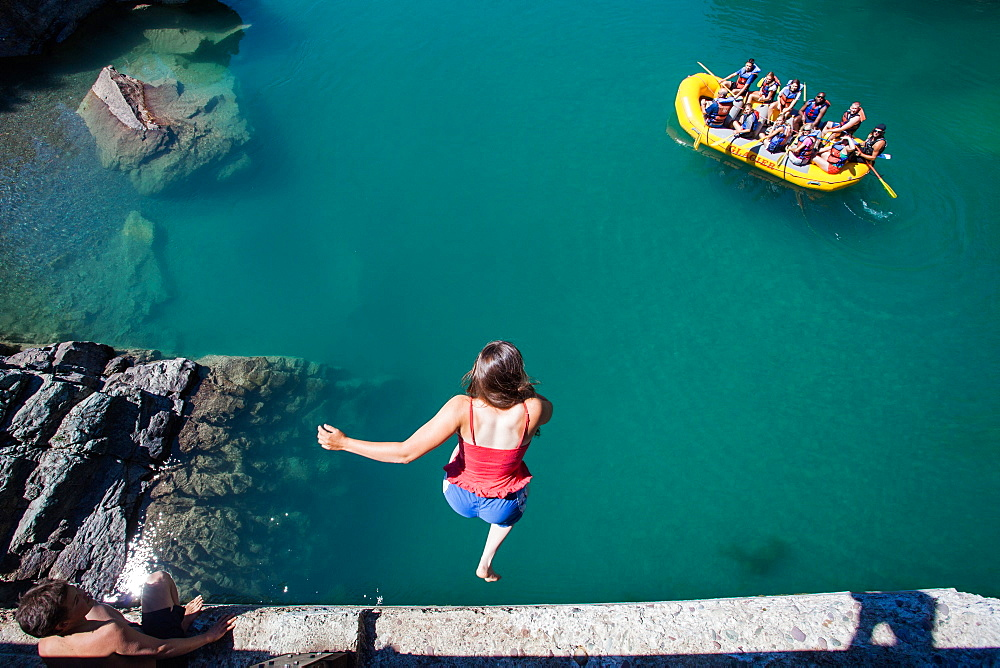 A girl jumps from a high bridge into a river of clear, blue-green water as a raft of people watches from below.
