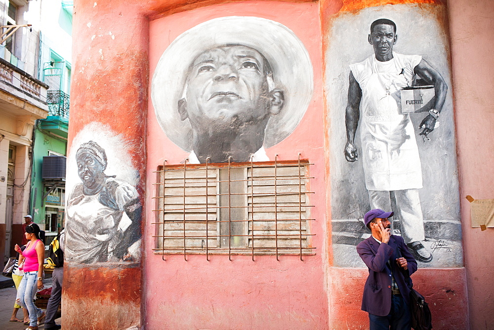 Pedestrians wait and walk by a mural painted on the side of a building in the old part of Havana, Cuba.