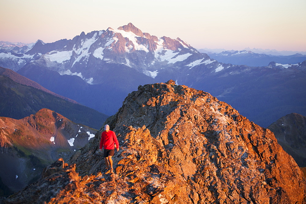 A hiker walks a rocky ridge with Mount Shuksan in the background, North Cascades National Park, Washington, United States