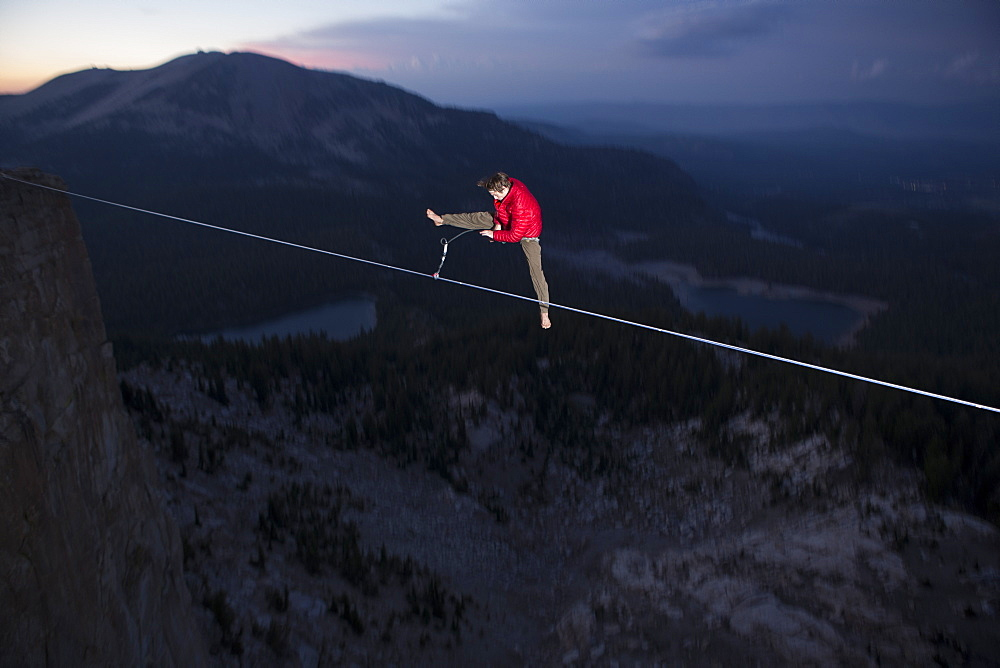 Male highliner jumps off a 125 foot highline over lakes in a gap on top of Mammoth Crest, Mammoth, California, United States