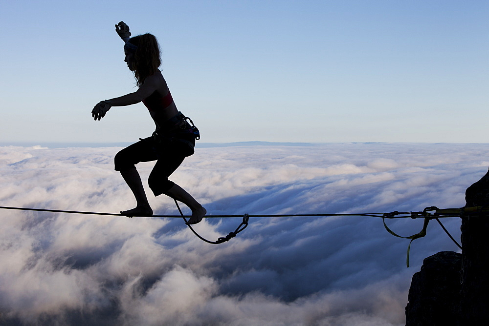 Silhouette of professional highliner Hayley Ashburn standing up on a highline above the clouds atop Mount Tamalpais, Marin County, California, United States