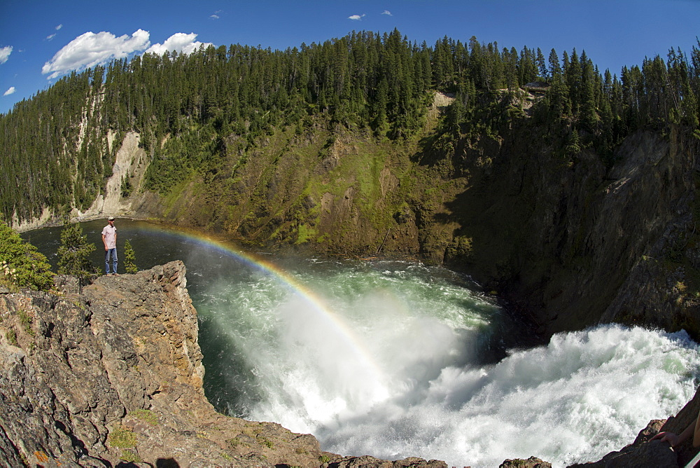 A man standing on a rocky point below a rainbow and next to the Upper Falls of the Yellowstone River in Yellowstone National Park, Wyoming, Yellowstone, Wyoming, usa