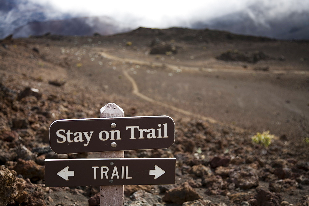 A sign telling hikers to stay on the trail in Haleakala crater. Hiking off-trail leads to significant soil erosion in the delicate volcanic soils, Maui, Hawaii, United States of America