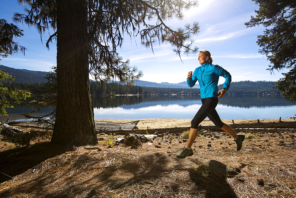 A female trail runner running next to Payette Lake in Ponderosa State Park, McCall, Idaho in the fall, Ponderosa State Park, McCall, Idaho, USA