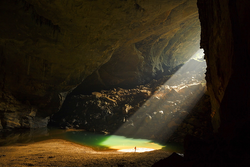 A caver stands in a sunbeam coming through an entrance to Hang En Cave in Phong Nha Ke Bang National Park, Vietnam. This natural phenomenon occurs only in the months of December and January.