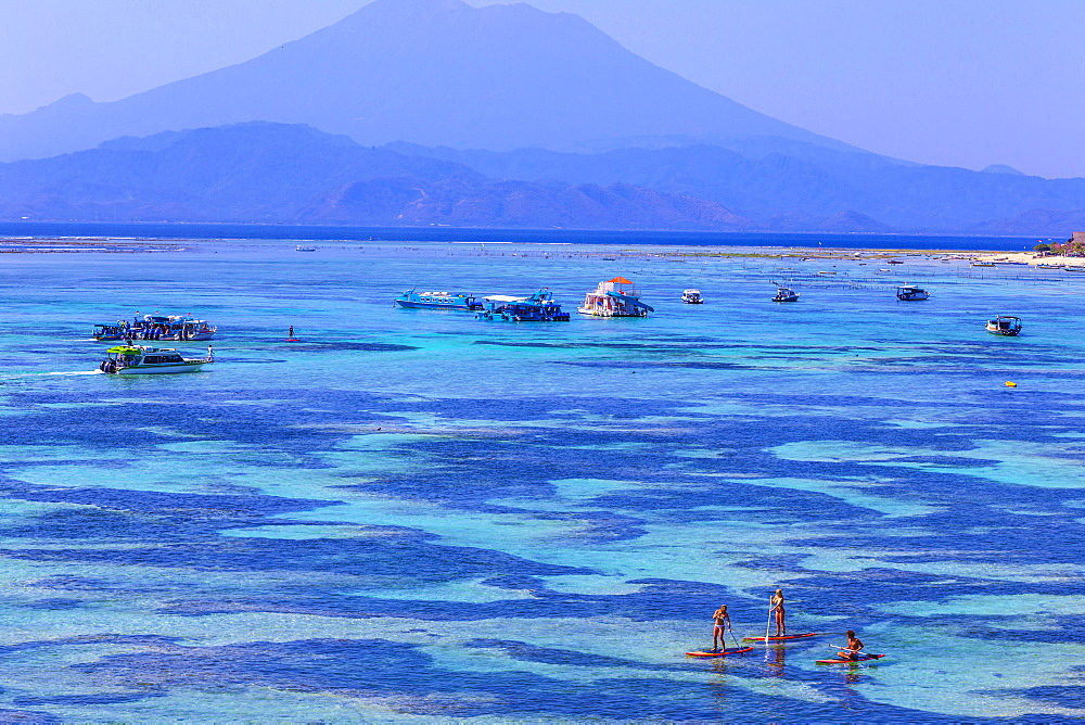 People travels by SUP surfboards at coastline of Nusa Lembongan and Nusa Ceningan islands, Indonesia.