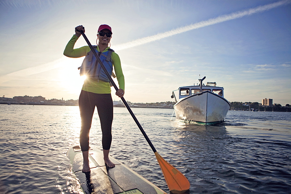 A smiling young woman paddleboards across the harbor in Portland, Maine at sunset.