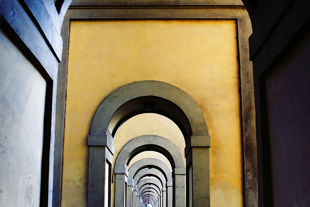 "Arched medieval stone walkway found at the end of the Ponte Vecchio (""Old Bridge"") next to the Arno River in Florence, or Firenze, Italy."
