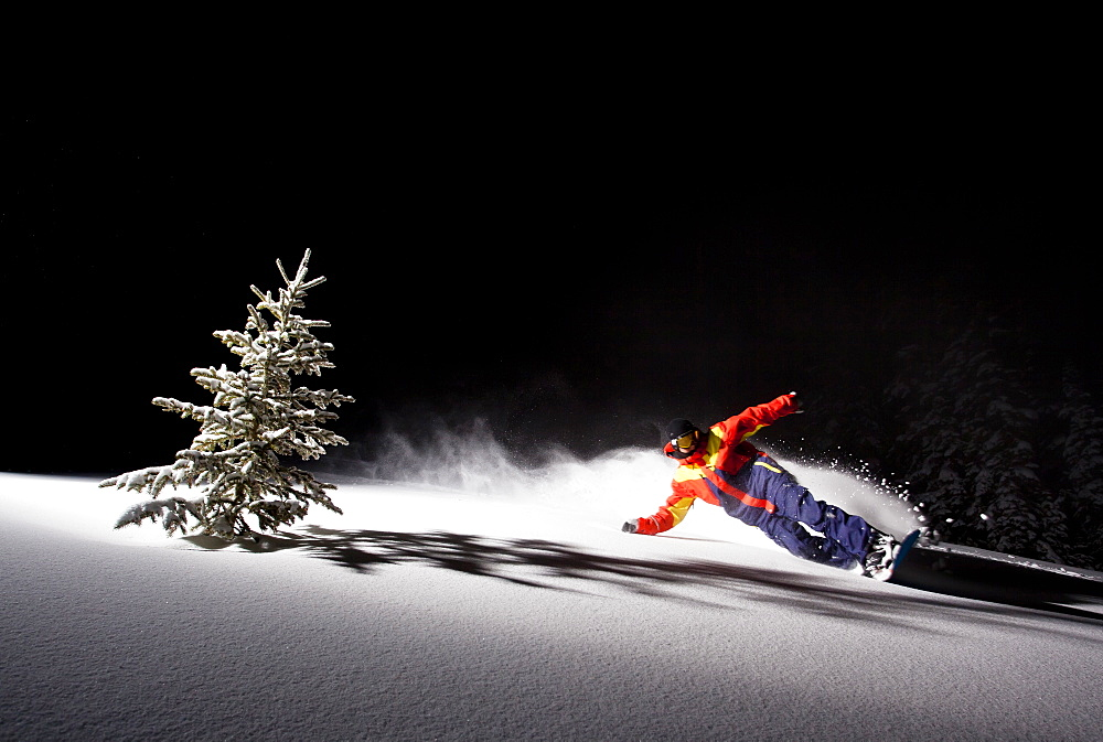 A man takes a powder turn around a single pine tree on Teton Pass at night.