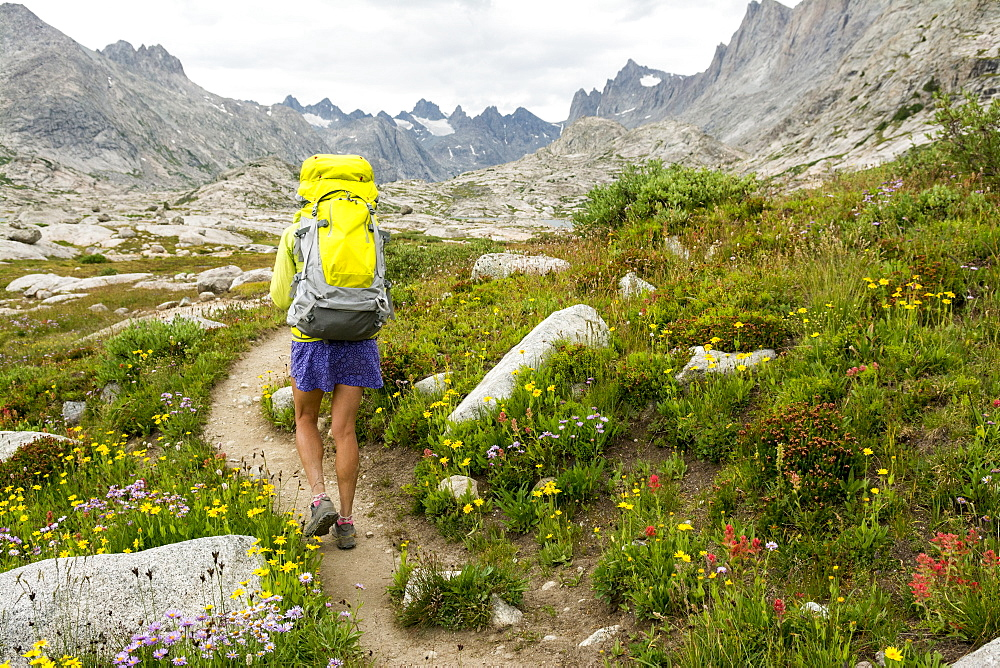 A woman hiking along trail into Titcomb Basin in the Wind River Range, Bridger Teton National Forest,  Pinedale, Wyoming.
