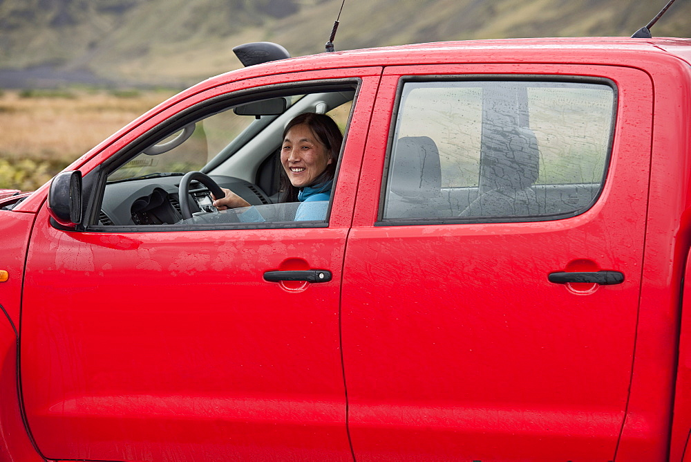 Woman driving red pick up truck in Iceland