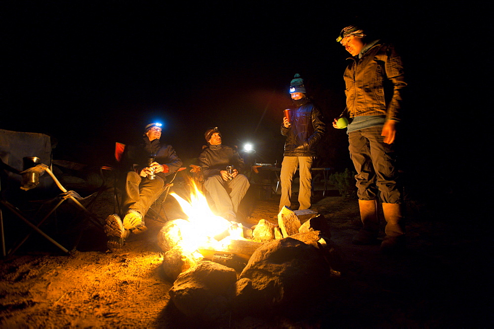 Dave Steiner, Ephraim Learned, Maria Hidalgo, and Chessa Jones sit around a campfire in Moab, Utah.