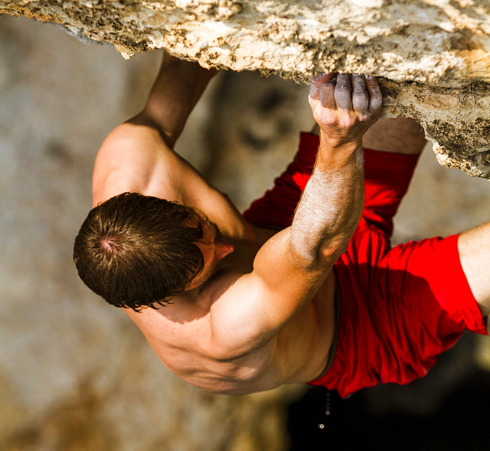 Belgium climber Siebe Vanheeat grabbing a hold as he is climbing a psicobloc route at the 2014 The North Face Kalymnos Climbing Festival; Greece.