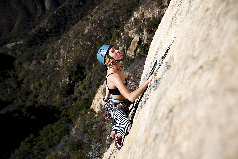 A woman wearing a tank top and striped pants reaches for chalk while climbing The Rapture (5.8) on Lower Gibraltar Rock in Santa Barbara, California.  The Rapture is a very nice and unbelievably well protected route on the left arête of Lower Gibraltar Rock.