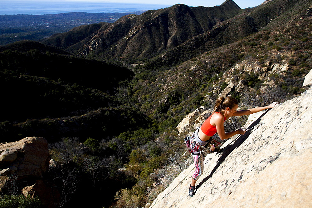 A woman wearing a red tank top and striped pants clips a quick draw while climbing The Rapture (5.8) on Lower Gibraltar Rock in Santa Barbara, California.  The Rapture is a very nice and unbelievably well protected route on the left arête of Lower Gibraltar Rock.