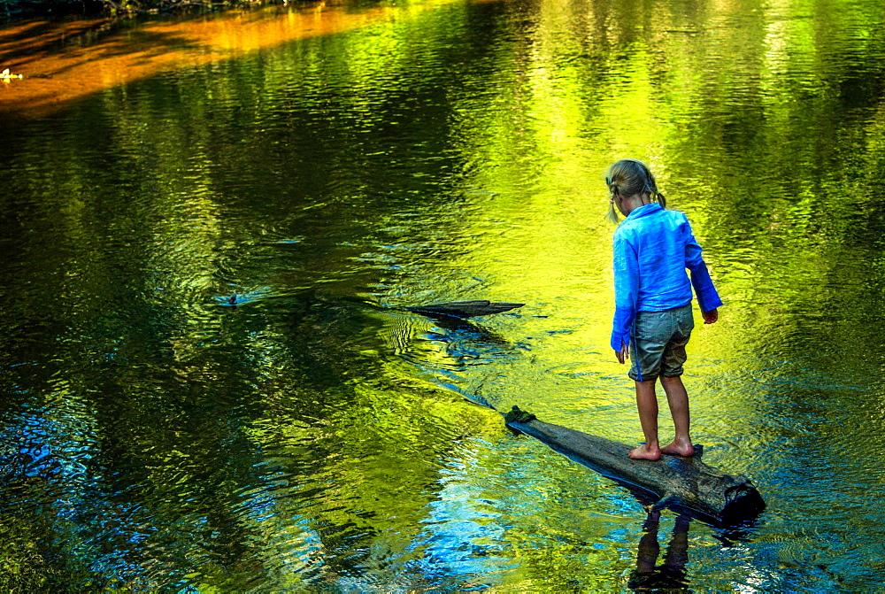 A girl walks on a submerged log near Hiawatha National Forest MI.