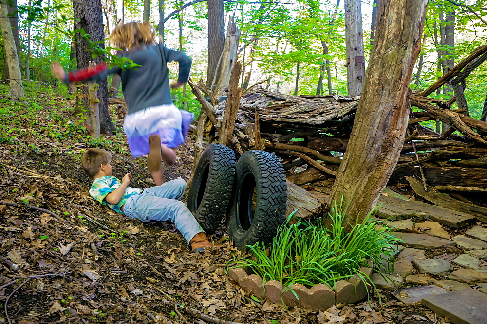 A girl jumps over a boy at their make shift hut in the woods at Pittsburgh PA. during the spring