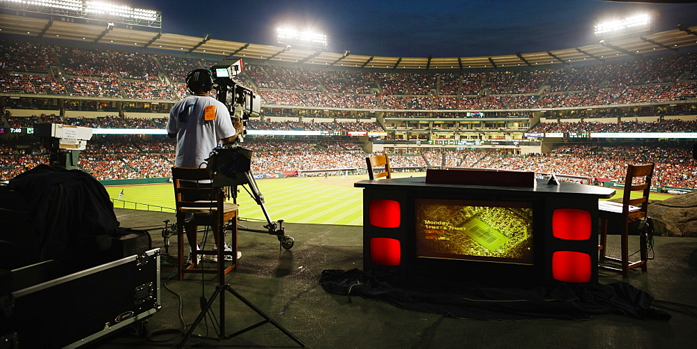 Rear view of a cameraman at a professional baseball game at Angel Stadium of Anaheim, California. USA.