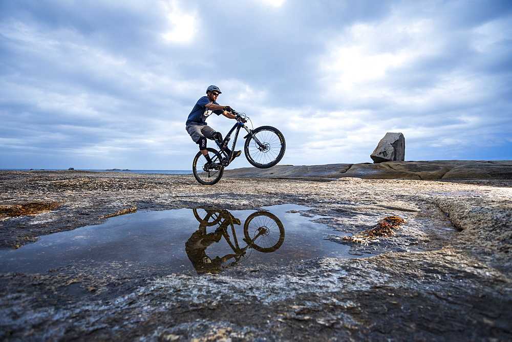 Male mountain biker riding on rocky foreshore near Bicheno blowhole on Tasmania's East Coast.