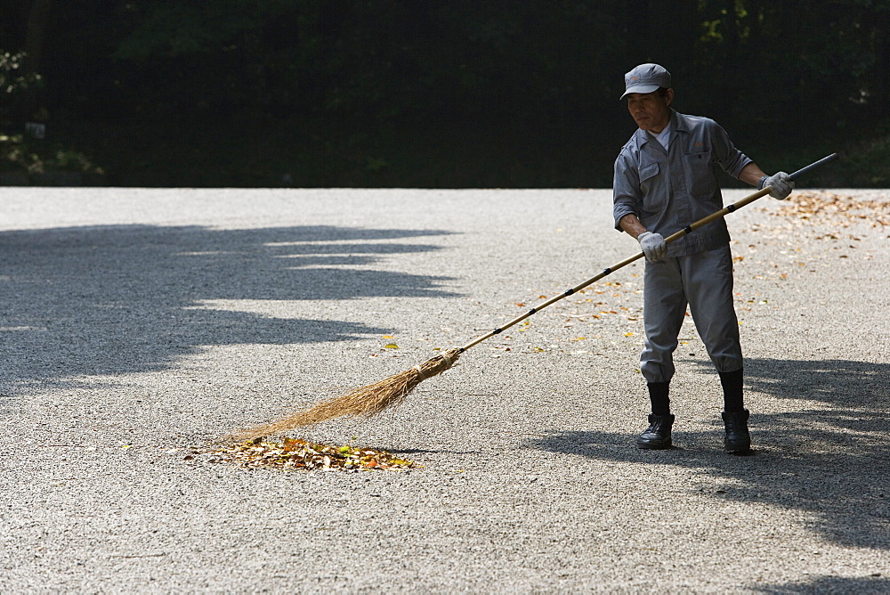 A man sweeping the walk way in a park, Tokyo, Japan.