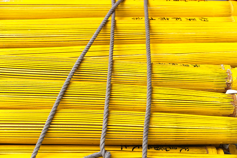 Close up of a stack of yellow closed umbrellas, Japan.