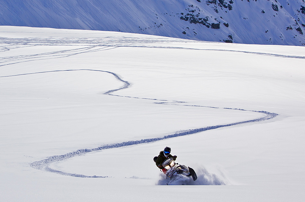 A women riders her snowmobile through a powdery field leaving the evidence of her turns behind her.
