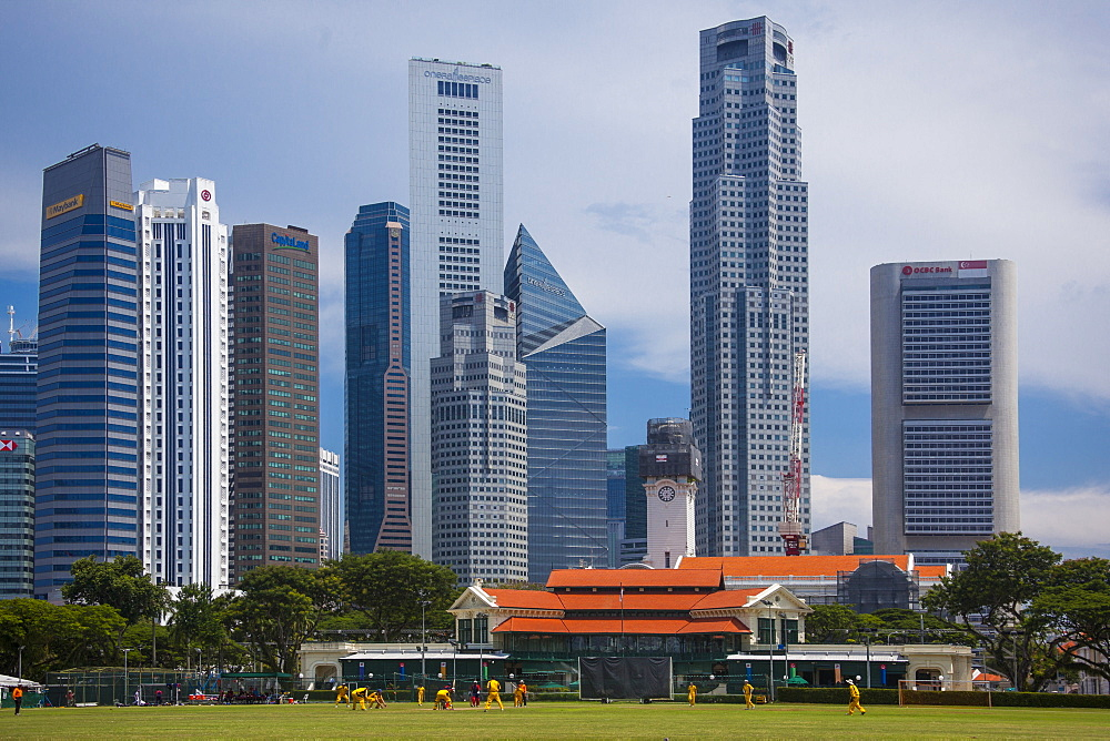 A cricket match goes on in front of the Singapore financial district skyline.