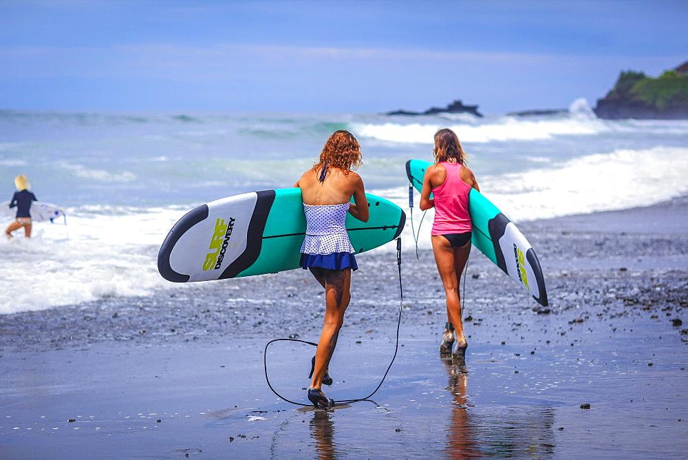 Surfer girls catch waves in high heels.