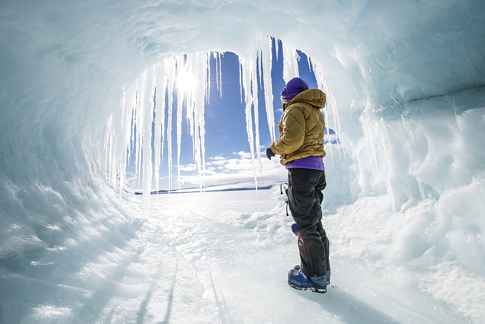 A woman looks out at the frozen Ross Sea from a hole in an iceberg.
