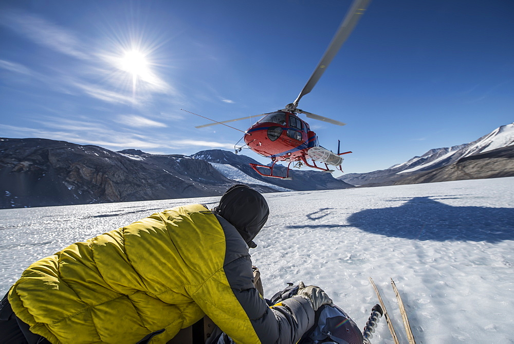 A scientist holds equipment while a helicopter lands next to him on the Taylor Glacier, Antarctica.